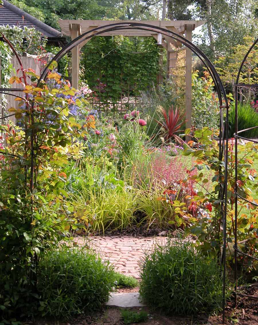 A summer garden border viewed through a cast-iron arch - showing a mutitude of planting, such as dusky pink poppies, blue Ceanothus, bright ornamental grasses