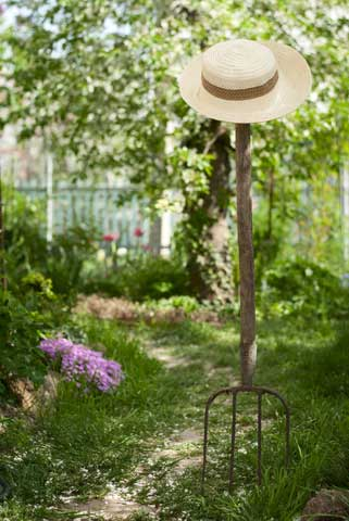 Garden fork stuck upright in the earth on the edge of garden border, straw sun hat perched atop.