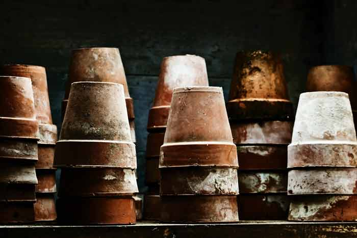 Weathered terracotta pots stacked upside down on a table.